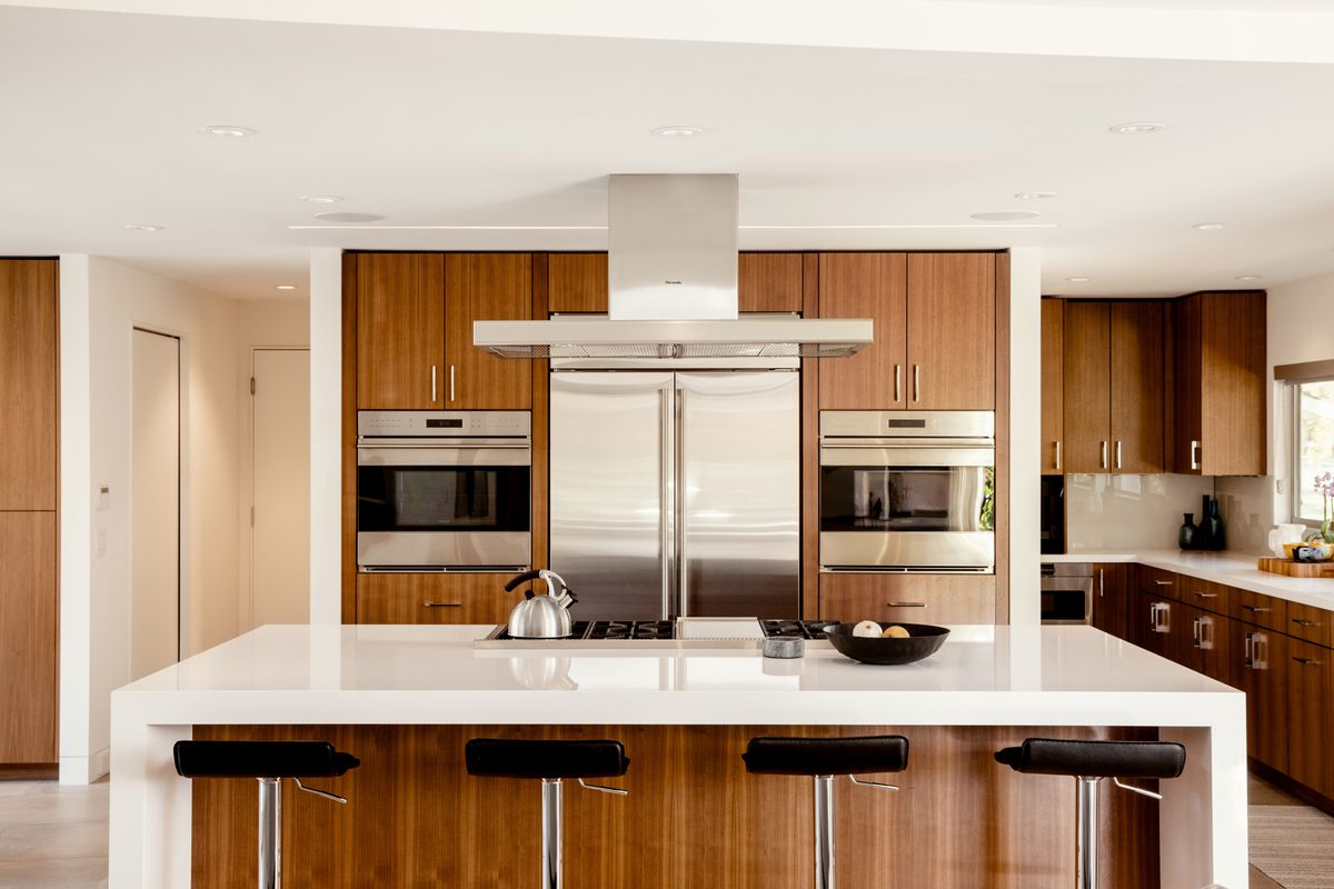 In the kitchen, brown walnut cabinets contrast with bright white countertops and stainless steel appliances.
