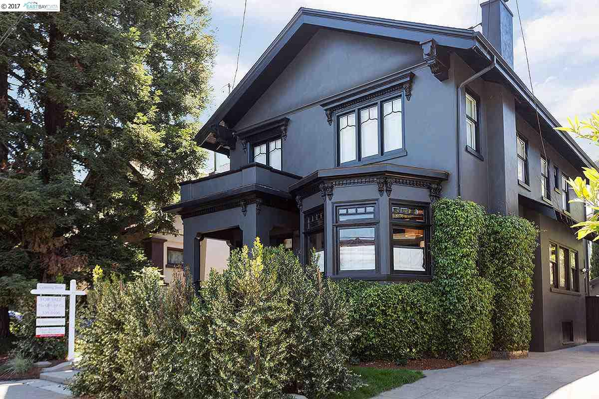 A black Craftsman home with bay windows on the first floor.