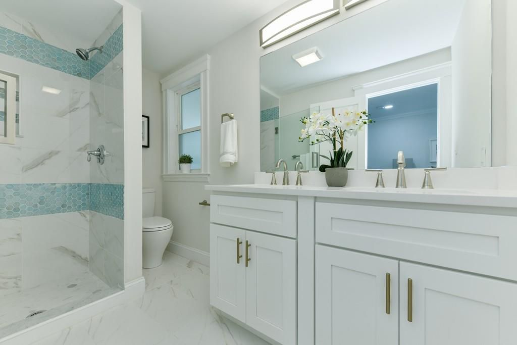 A bathroom with two sinks and a toilet next to a shower.