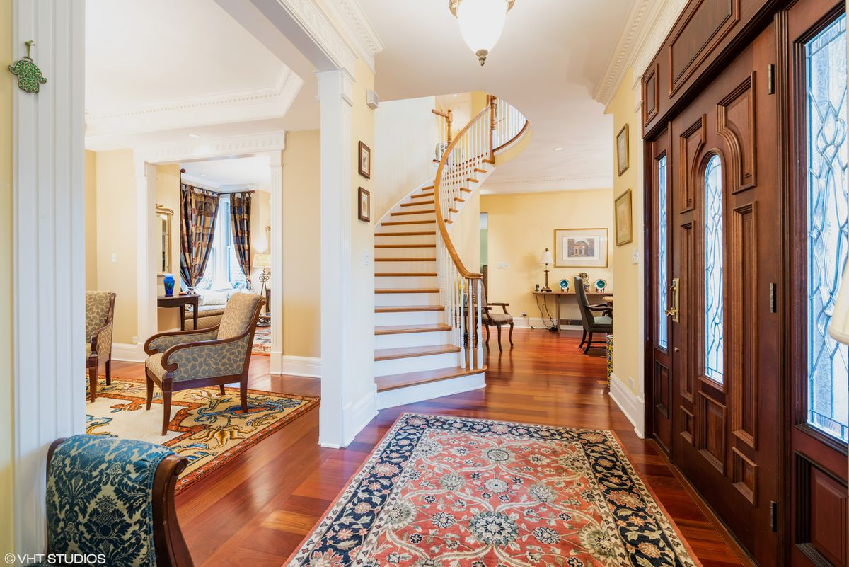 A grand foyer with a curved staircase, art glass, vintage rugs, and crown molding.