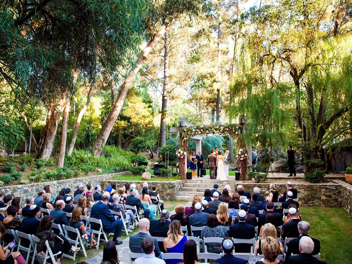 Many people are sitting in chairs outside at Calamigos Ranch's historic Redwood Room surrounded by oak and eucalyptus trees.