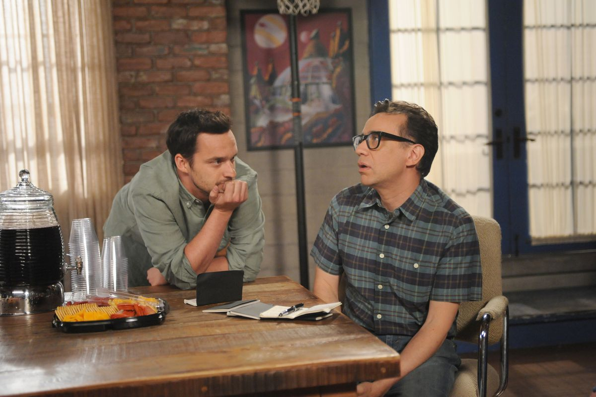 Nick (Jake Johnson, left) talks to one of the guests staying in his apartment, played by Fred Armisen.