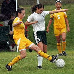 Cyprus's Jessica Frank kicks the ball past Olympus's McCall Miles during Tuesday's windy, rainy contest at Olympus High School.