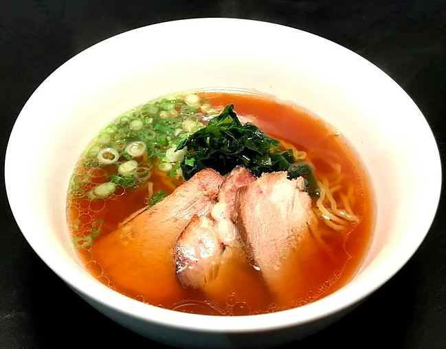 A dark brown broth with three pieces of pork, chopped green onions, and noodles in a white bowl