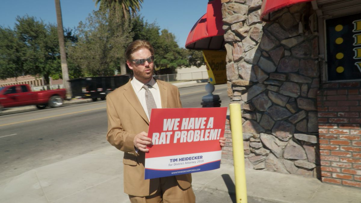 """Tim Heidecker wears shades and holds a """"We Have a Rat Problem"""" campaign sign"""