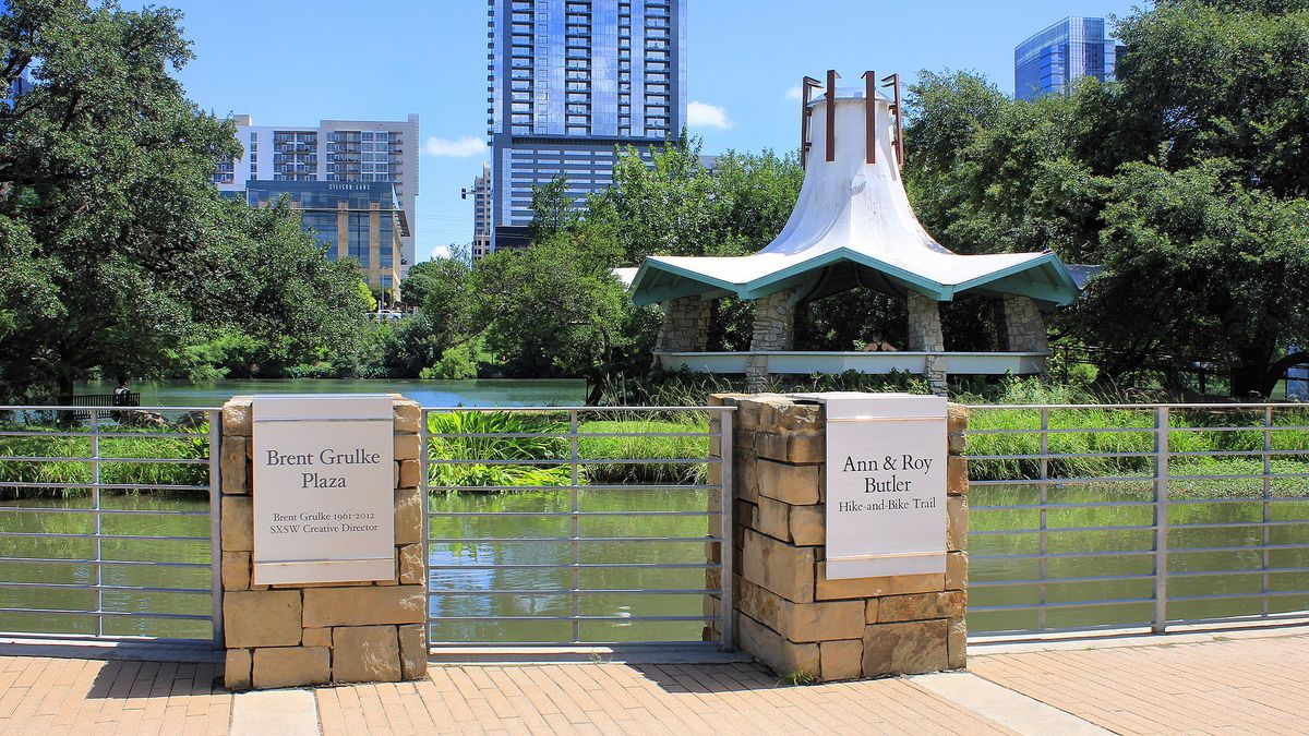 Plaza with memorial markers, midcentury style gazebo, river, downtown buildings