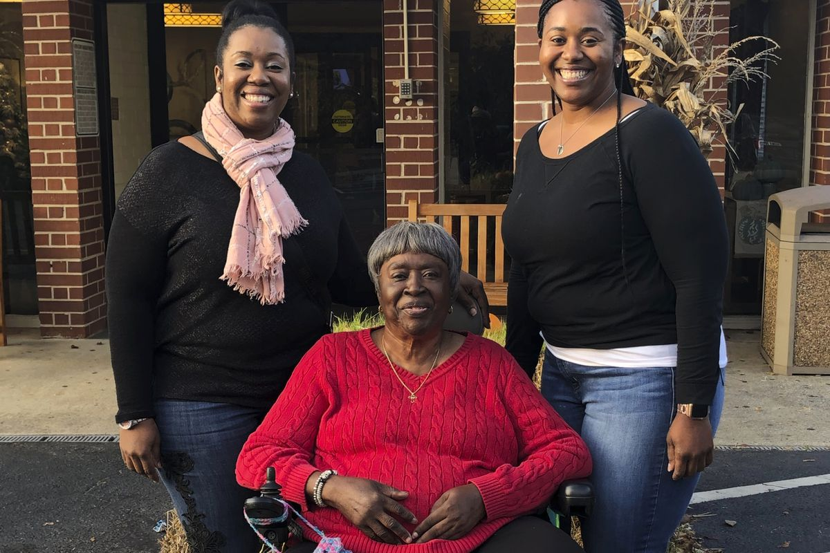 In this Nov. 28, 2019, photo provided by the Burrough family, Bessie Burden, center, poses with her daughters Theresa Burrough, left, and Lashieka Mitchell outside the Westbury Conyers nursing home in Conyers, Ga.
