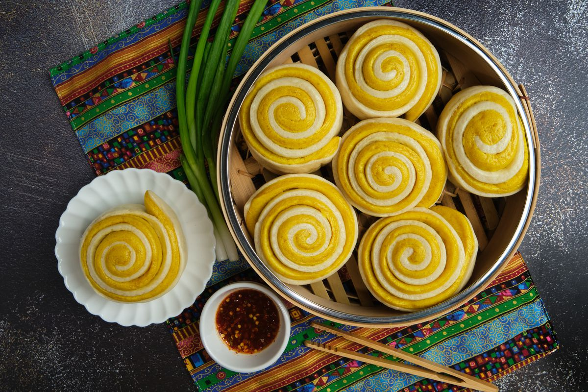 A basket of pinwheel-shaped tingmomo sit in a steamer basket next to some scallions, a pair of chopsticks, and a small white bowl of red chili sauce, along with a single tingmomo on a white plate. Everything sits on top of a colorful placemat.