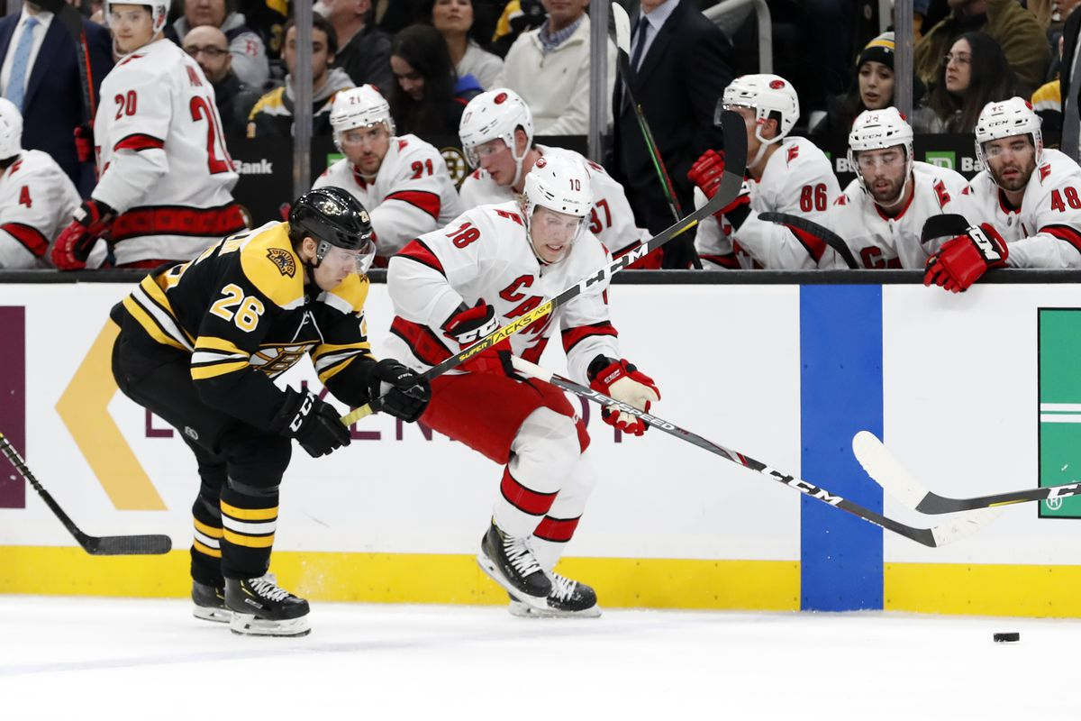 Carolina Hurricanes left wing Ryan Dzingel tries to get past Boston Bruins center Par Lindholm during a game between the Boston Bruins and the Carolina Hurricanes on December 3, 2019, at TD garden in Boston, Massachusetts.