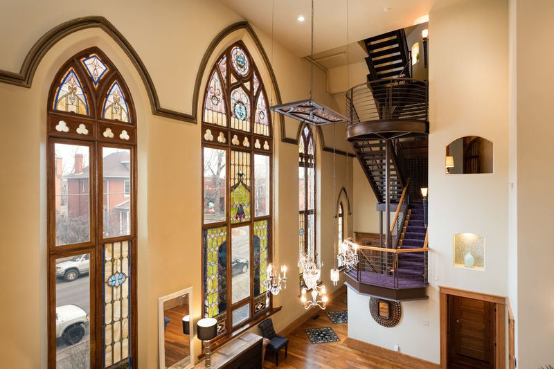 A church turned house features tall stained glass windows on one wall and very tall ceilings.