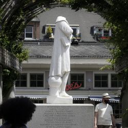 Passers-by walk near a damaged Christopher Columbus statue, Wednesday, June 10, 2020, in a waterfront park near the city's traditionally Italian North End neighborhood, in Boston. The statue was found beheaded Wednesday morning, Boston Mayor Marty Walsh said.