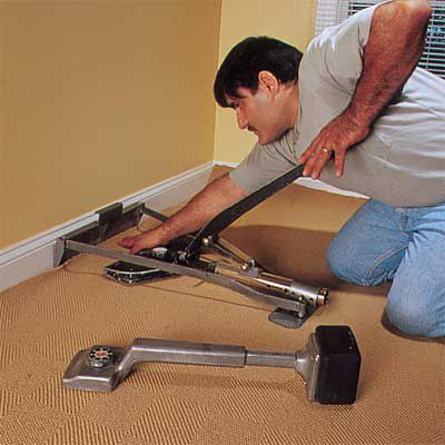 Man Uses Lever-Activated Stretcher To Stretch Carpet