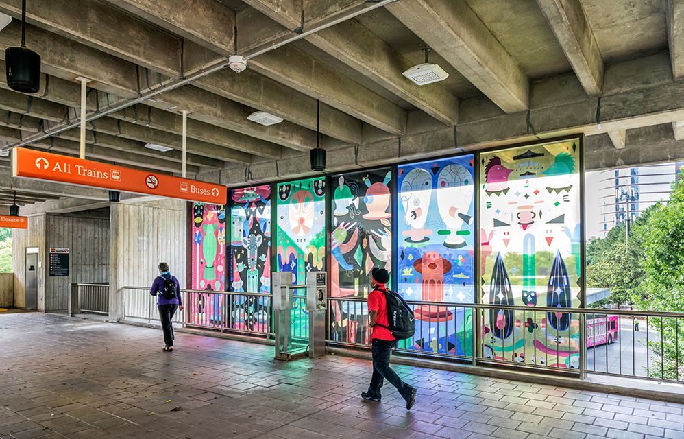 Six window panes inside the MARTA station are decorated with colorful, abstract designs.
