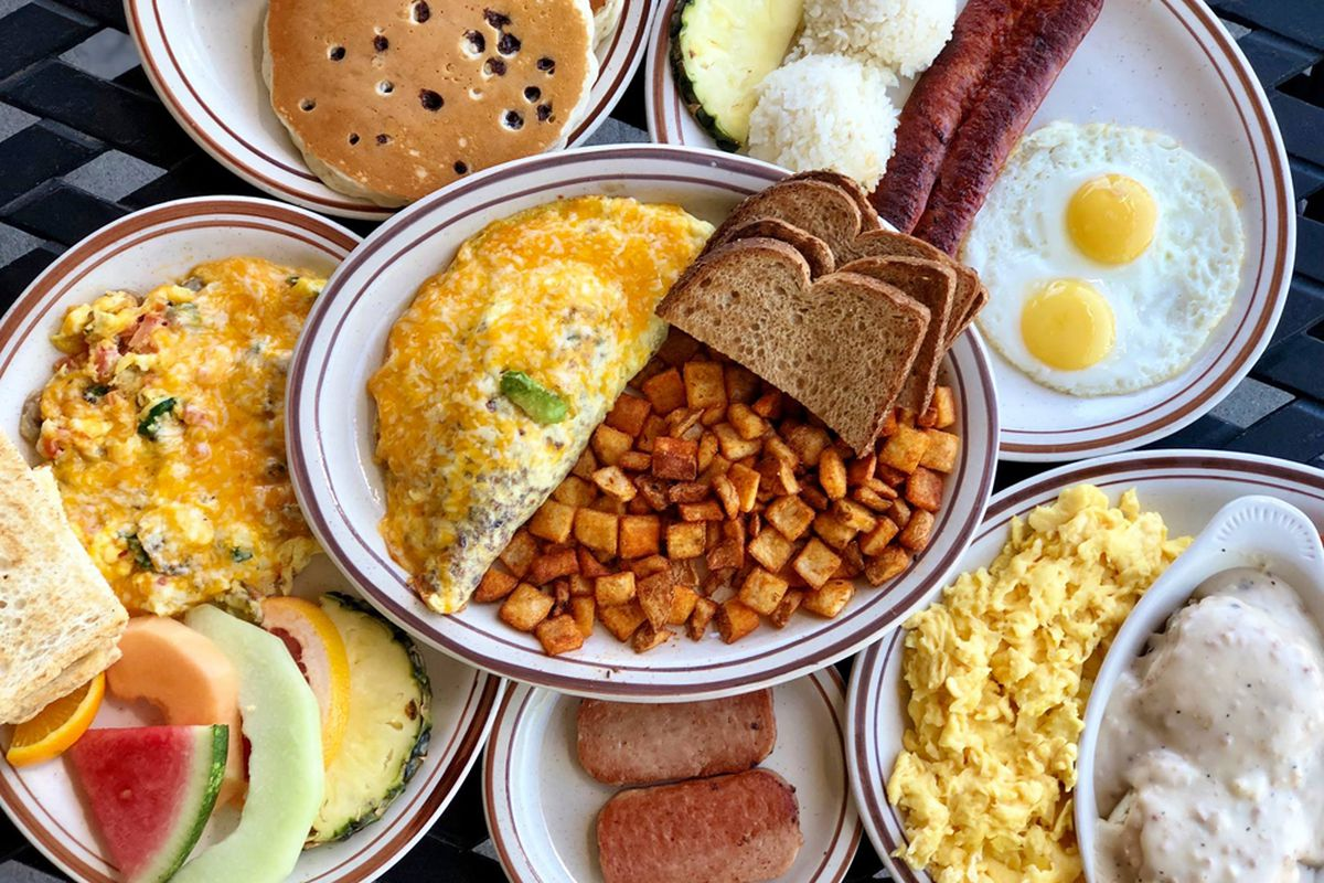 A table of breakfast favorites served at Egg works, including pancakes, biscuits and gravy and grilled spam.