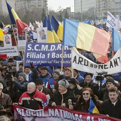Anti-government protesters wave various banners during a protest march in Bucharest, Romania, Tuesday, Jan. 24, 2012. Some thousands, from all over Romania, joined protests in the Romanian capital asking for the resignation of the country's president and early elections.