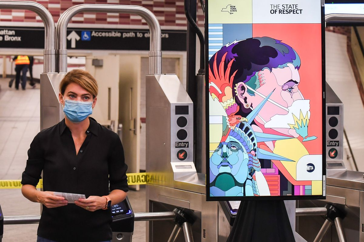 New York City Transit President Sarah Feinberg stands next to a video screen Atlantic Avenue-Barclays station in Brooklyn during a news conference to promote mask wearing, Sept. 14, 2020.