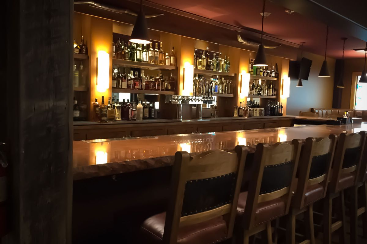 A view of a softly lit bar, counter, and chairs at Rooster's Bar and Grill in Capitol Hill.