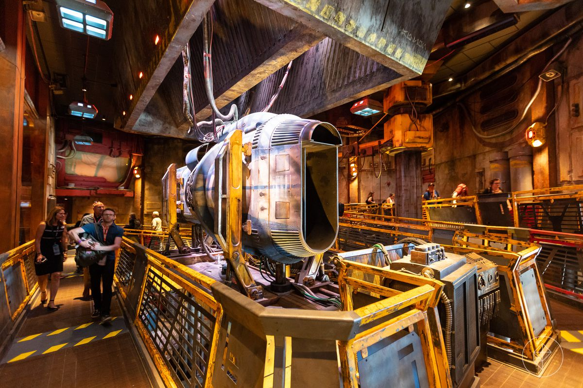 The interior of a building at Galaxy's Edge in Disneyland. There are industrial machines and parts in the center of a room.