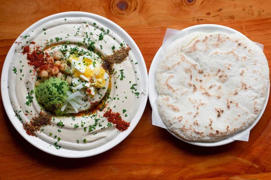 A bowl of hummus sits next to a fresh pita