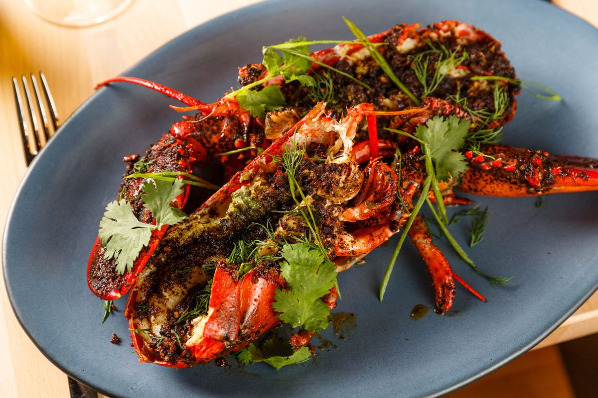 A lobster with black bean butter on a blue plate, next to a fork