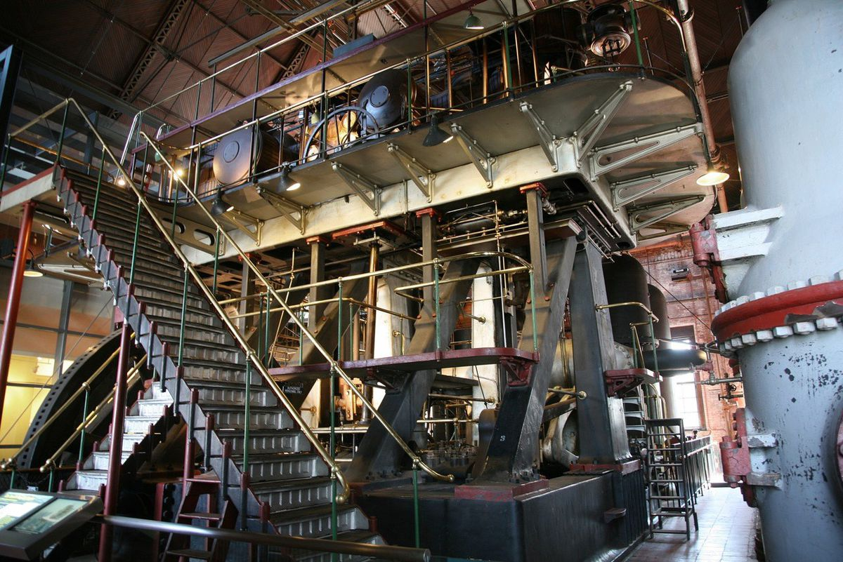 The interior of an elaborate engineering museum, with many pipes and metal stairs.