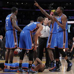 CORRECTS SPELLING OF NAME TO METTA, NOT META - Oklahoma City Thunder players stand over teammate James Harden, lower left, after receiving a flagrant double foul from Los Angeles Lakers' Metta World Peace, who was then ejected, in the first half of an NBA basketball game, Sunday, April 22, 2012, in Los Angeles.