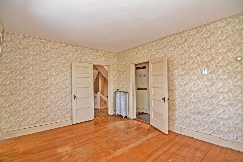 An empty bedroom with a door opening into the hallway and another into a closet.