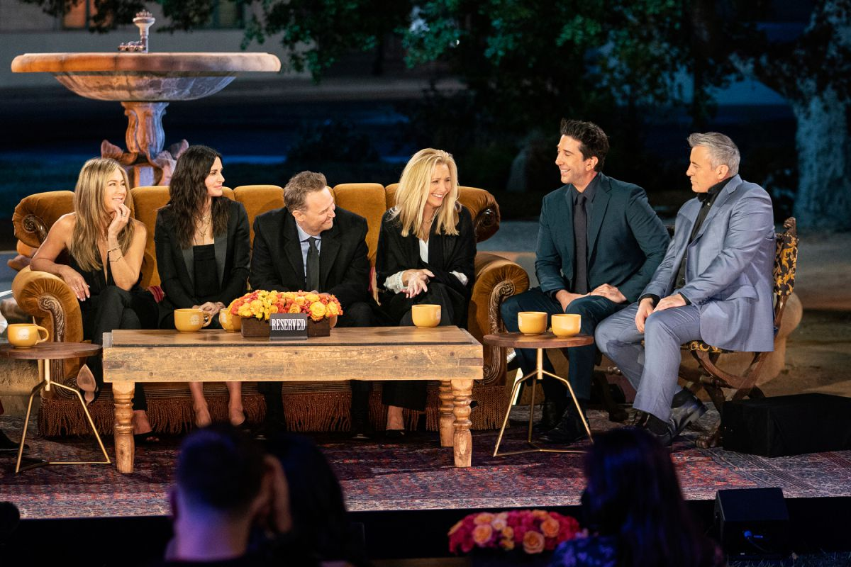 All six Friends cast members sit on couches and chairs, smiling and talking.