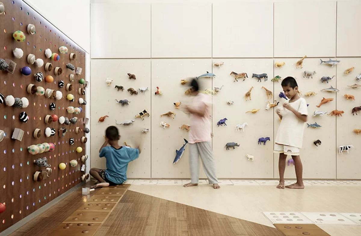 Kids playing with pegs on wall