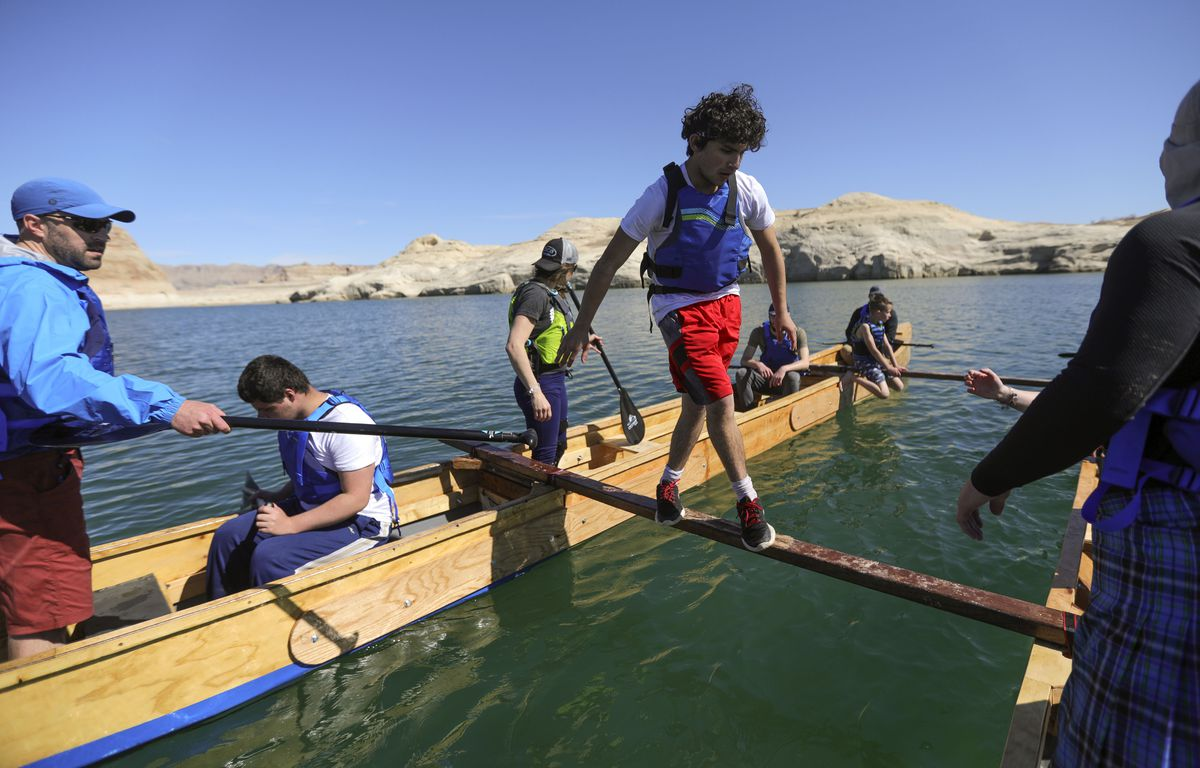Noah Isaac Mason, who is legally blind due to retinoschisis, crosses a slippery, narrow plank to change positions and redistribute weight in the boats as members of the Utah Schools for the Deaf and the Blind Yacht Club train on Lake Powell on Saturday, March 27, 2021. They are training for the SEVENTY48, a 70-mile human-powered boat race from Tacoma to Port Townsend, Wash.