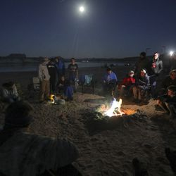 Members of the Utah Schools for the Deaf and the Blind Yacht Club gather with members of Colorado's Platte Canyon High School Yacht Club around a campfire after a long day of training at Lone Rock Beach at Lake Powell on Saturday, March 27, 2021. Both teams are training to race their handmade boats in the SEVENTY48 from Tacoma to Port Townsend, Wash.