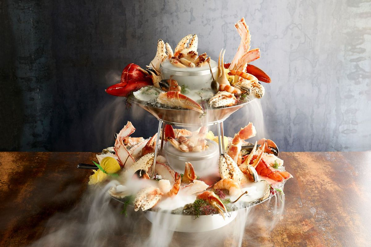 Glamour shot of a multi-tier seafood tower, garnished with plenty of crab claws and dry ice