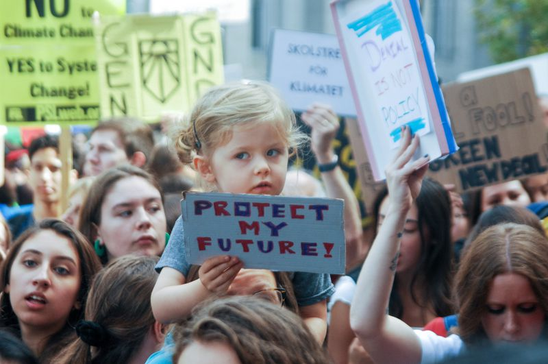 """In a crowd of protesters, a small child on its parent's shoulders holds a sign that reads, """"Protect my future!"""""""