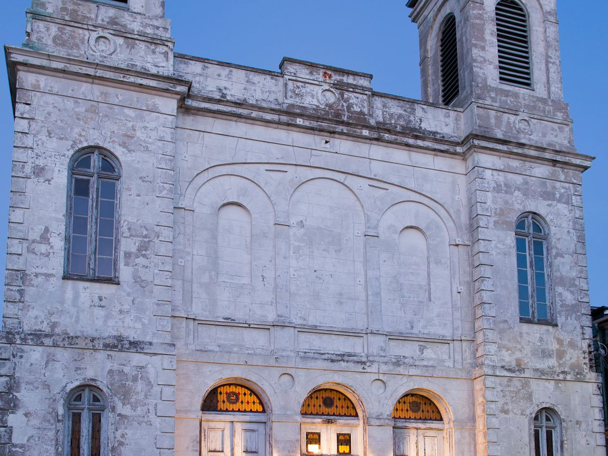 The exterior of the Marigny Opera House. The facade is white and there are multiple arched doors and windows. There are two towers.