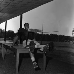 1964-FSU football player Les Murdock lifting weights after practice in Tallahassee.