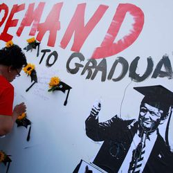 """A woman visits a mural at the """"End of School Year Peace March and Rally"""" in Chicago. 