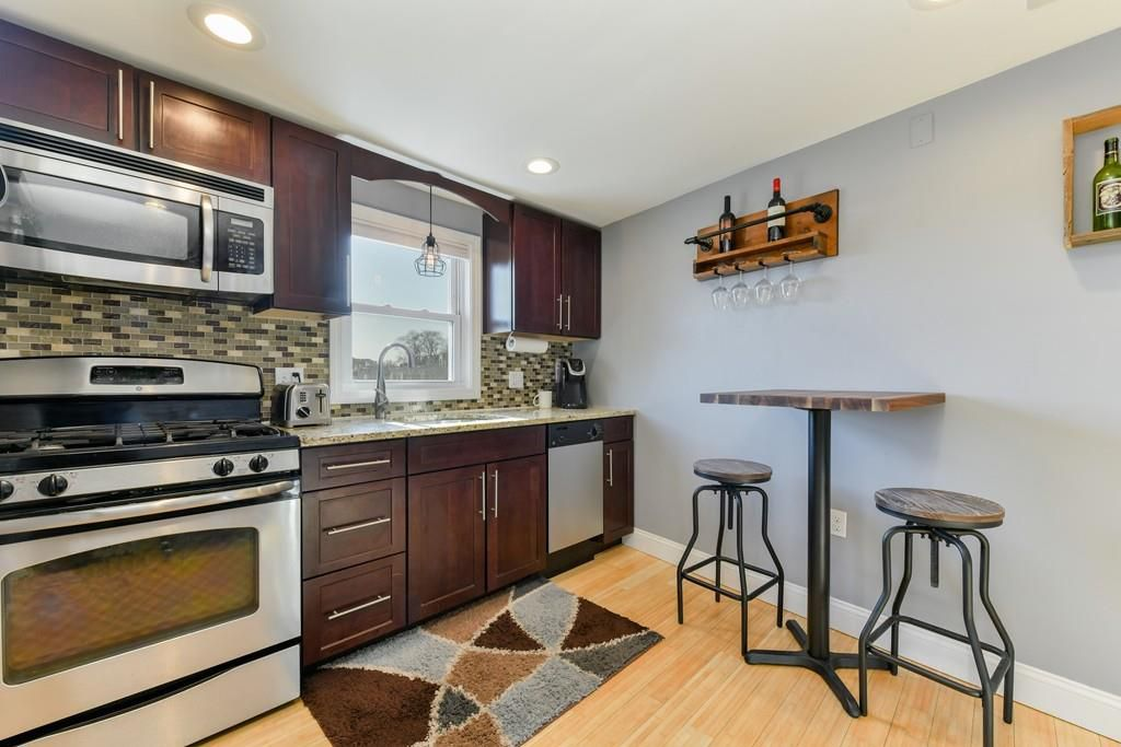 A small open kitchen with a table and two chairs.