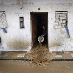 A man to clear muddy water from his house, after heavy rain caused flash floods in the town of Villanueva del Rosario, Malaga, southern Spain, Friday, Sept. 28, 2012. Homes were destroyed and at least one woman was killed. Rescue workers are searching to determine if there are more victims.