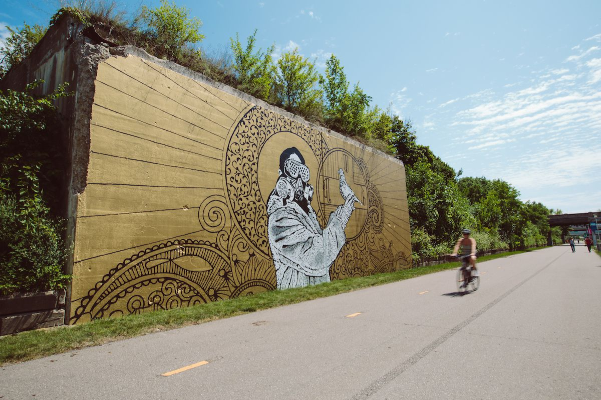 A mural depicting a person in a gas mask is on a wall in Detroit.