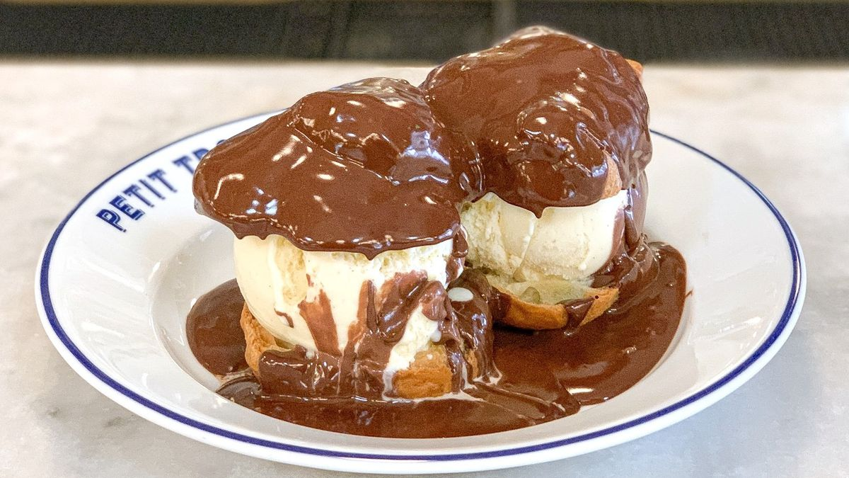 Two profiteroles with ice cream and chocolate sauce on a plate.
