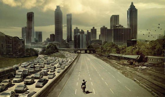A scene from the Walking Dead where Rick is on a highway. One side of the highway is empty. The other side of the highway has many cars which are all standing still. In the distance is a city skyline with many tall buildings.