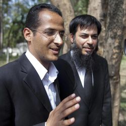 CORRECTING NAME OF LAWYER TO ATIF ALI KHAN - Zakariya Ahmad Abd Al-Fattah, brother-in-law of Bin Laden, left,  faces the media cameras as he leaves the house where Osama bin Laden's family are being detained,  with lawyer Atif Ali Khan, right, in Islamabad, Pakistan, on Monday, April 2, 2012.  The lawyer for Osama bin Laden's family says a Pakistani court has convicted his three widows and two of his daughters on charges of illegally living in Pakistan and sentenced them to 45-days in prison.