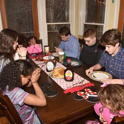 The DeGarmo family — Gracie, Jace, Kelly, Brailey, John, friend of the family Matthew Updike, Brody and Cassie — enjoy breakfast in their home.