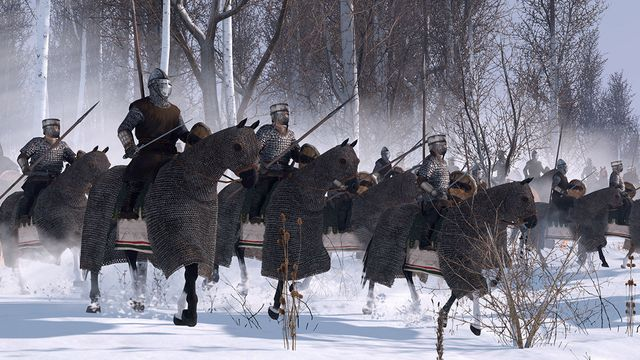 A battle line of mounted knights stands on the edge of a wooded field.
