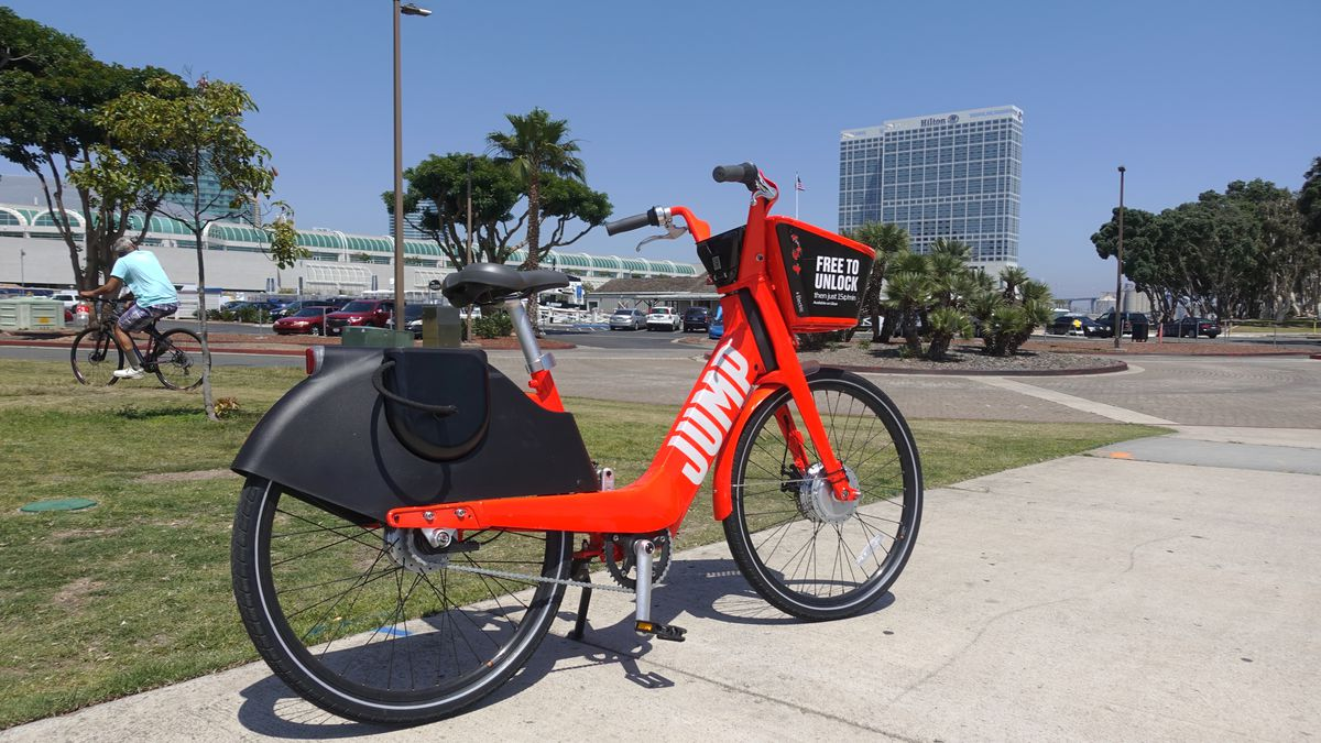 A bright red dockless electric bike is seen parked on a sidewalk along a busy bike trail with tall buildings of downtown San Diego in the background.