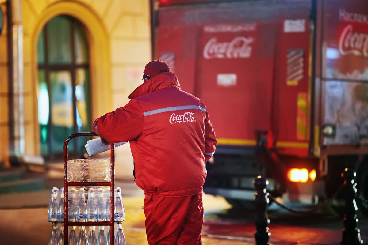 A person in a red Coca-Cola jacket pushing a dolly cart with packed beverages next to a Coca-Cola truck
