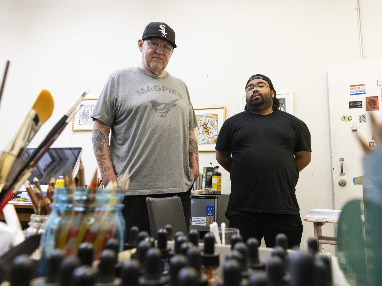 Muralists Tony Fitzpatrick, left, and Danny Torres, right, pose for a portrait at their studio in Wicker Park on Friday.