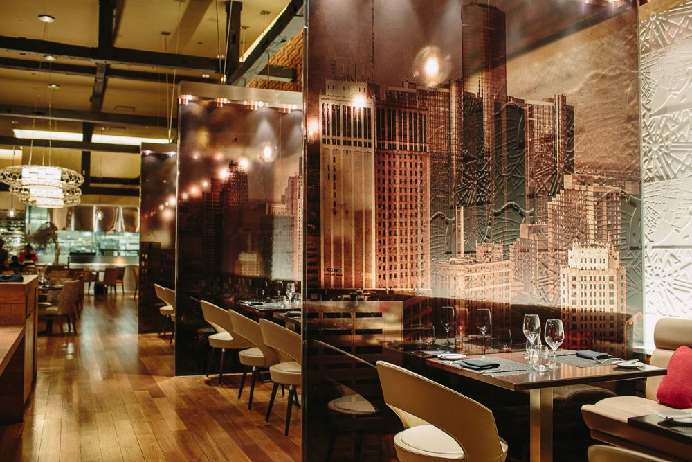 The dining room at Wolfgang Puck Steak has sepia toned wallpaper with the Detroit skyline printed on it and tables separated by black, see-through glass with white chairs surrounding the tables.
