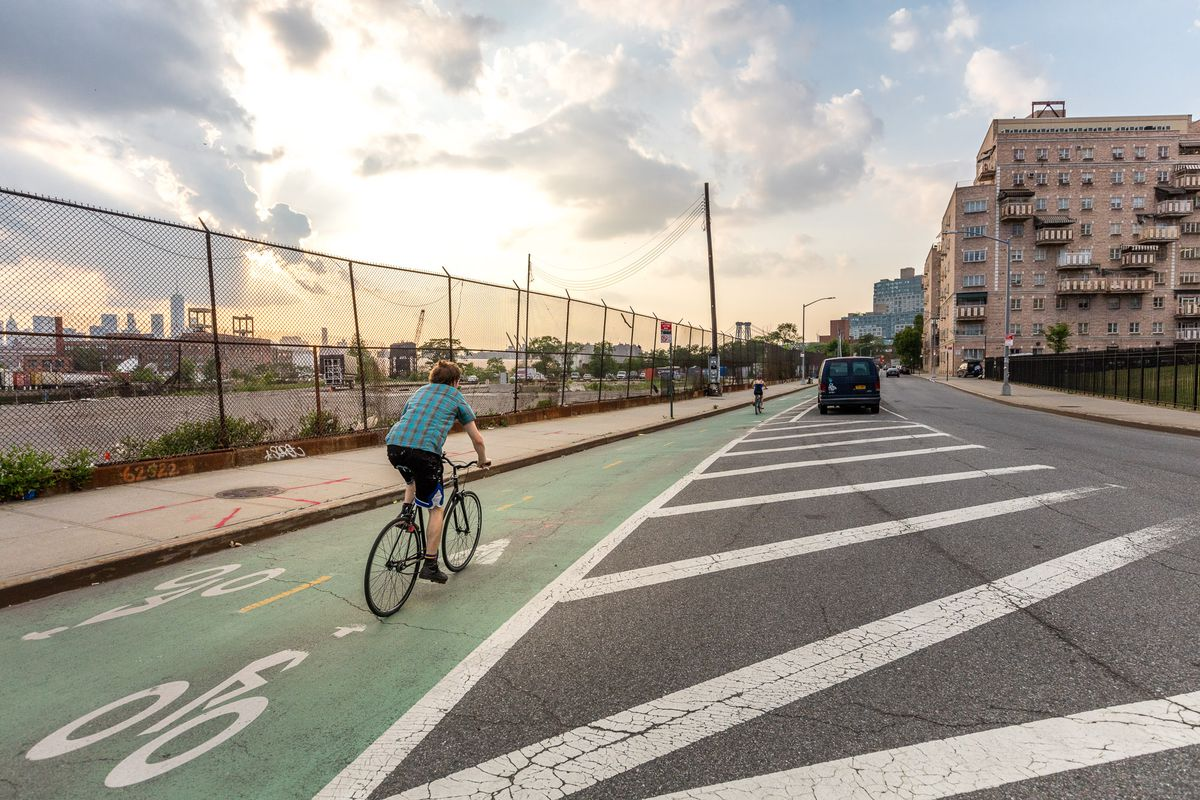 A young boy riders a bike in a green, parking-protected bike lane.