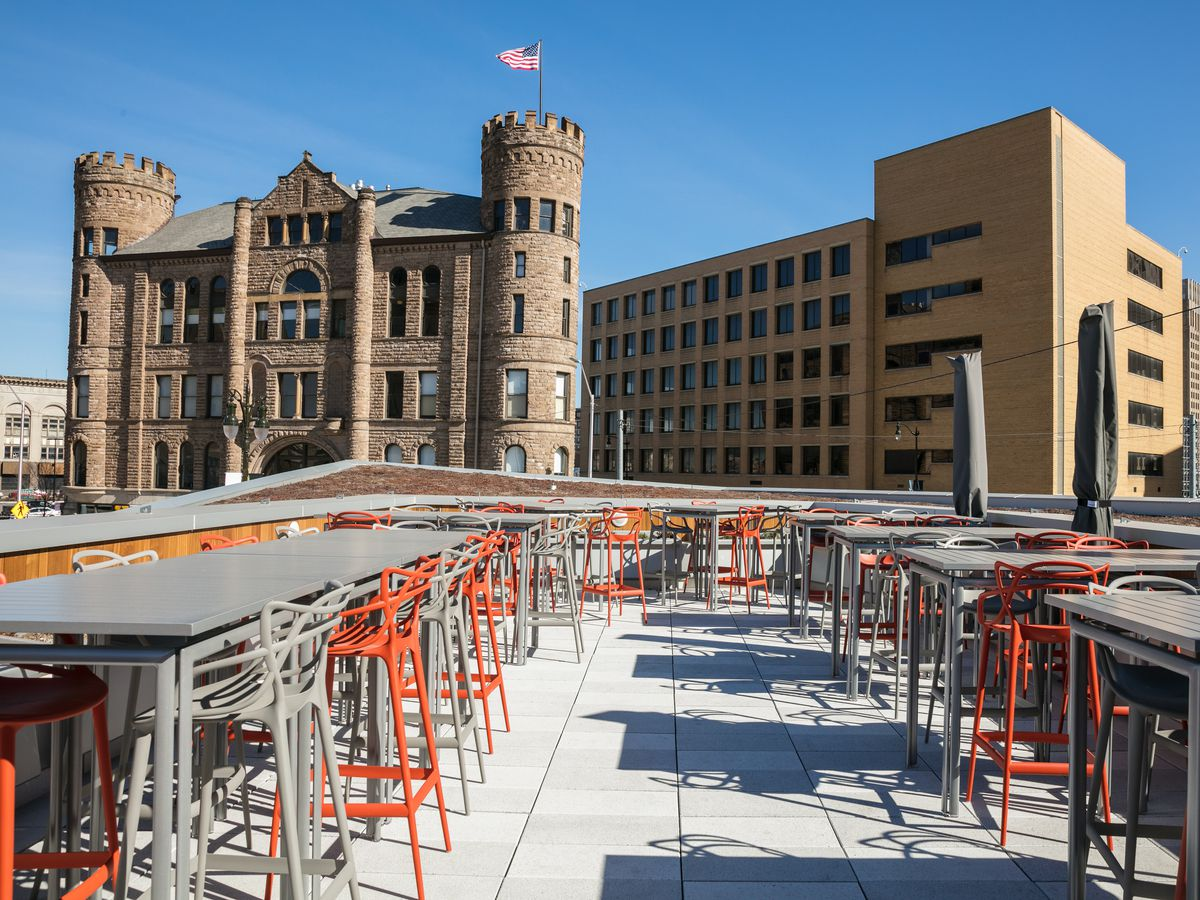 Tables and chairs on the rooftop of a building overlook a skyscraper
